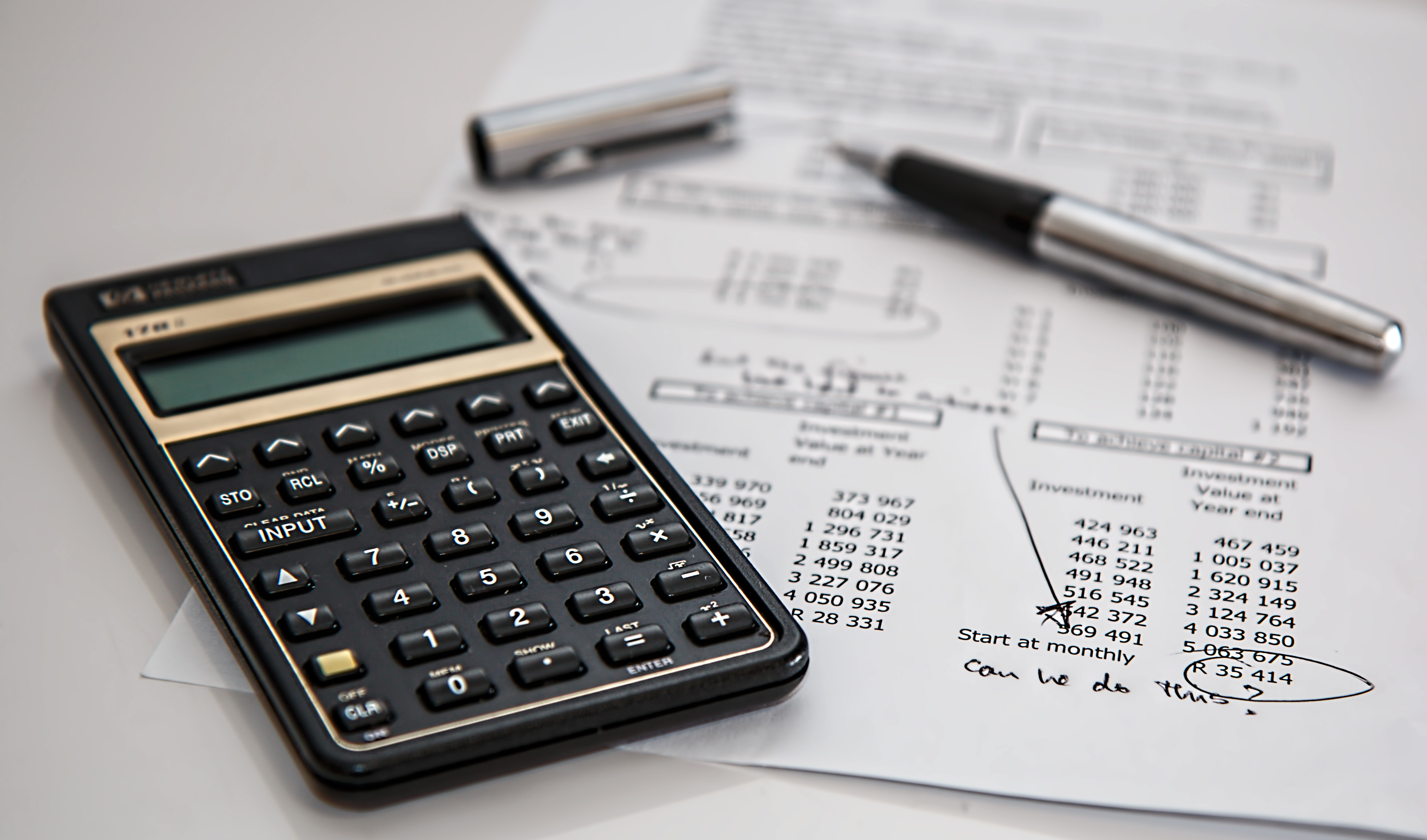 image of calculator on top of a pile of finance paperwork