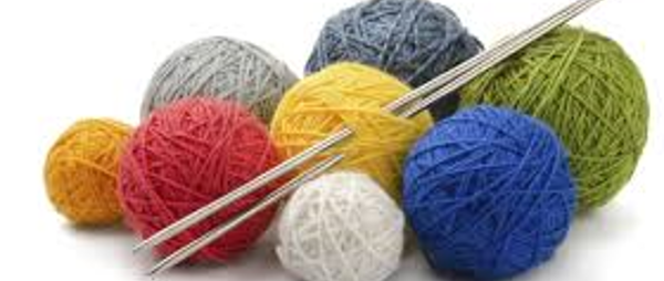 image of several balls of wool with some knitting needles going through them