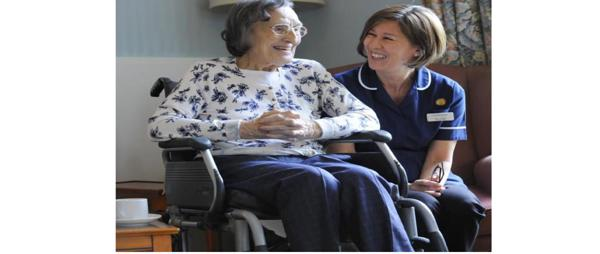 image of a elderly women sitting in a chair talking to a nurse who is crouched down