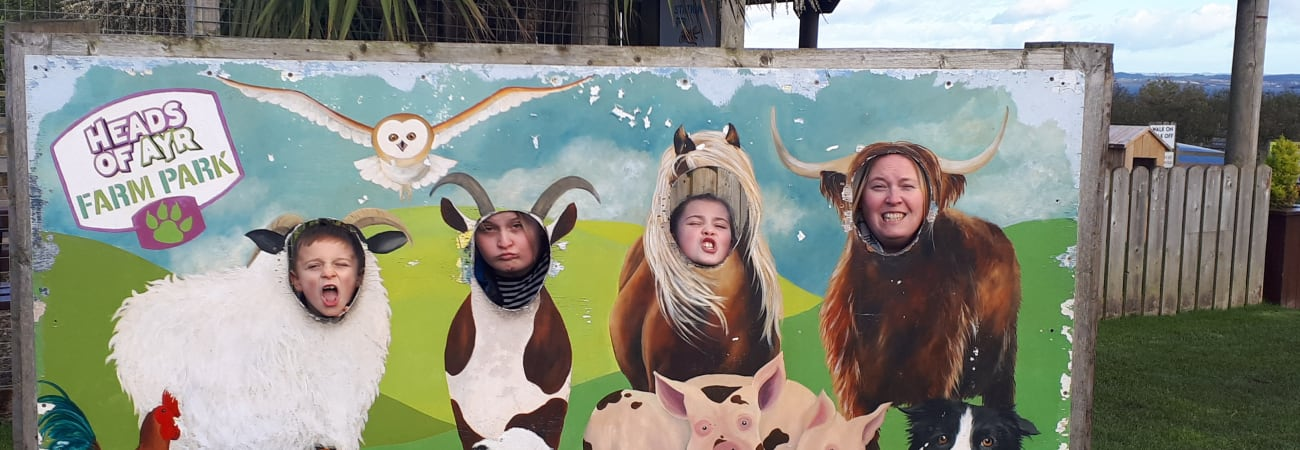 Picture of family sticking their heads in animal cut out wall