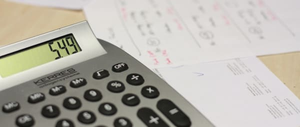 image of a scattered paperwork with a calculator sitting on top of them